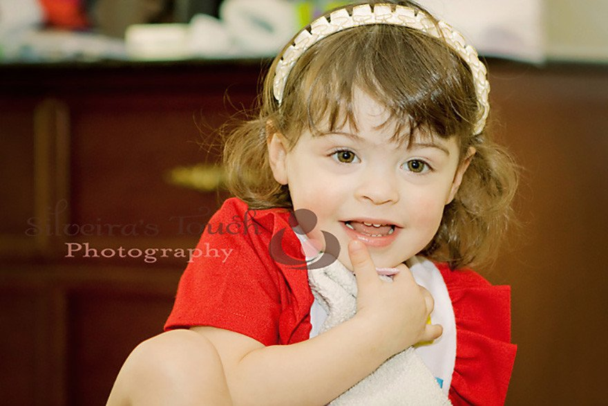 ny family photography of baby girl wearing red holiday dress smiling