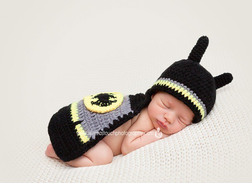 newborn photography of baby wearing batman costume