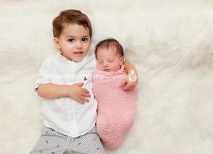 Livingston NJ newborn photography of siblings laying on white fur rug