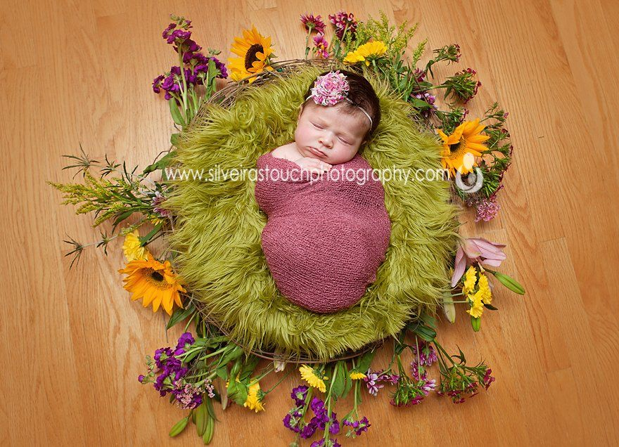 Newborn photography of baby girl on a nest of flowers sleeping