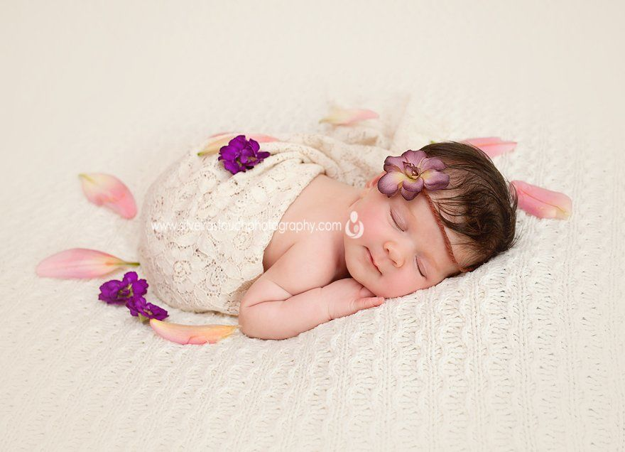 Newborn photography of baby girl sleeping with flowers in VErona NJ