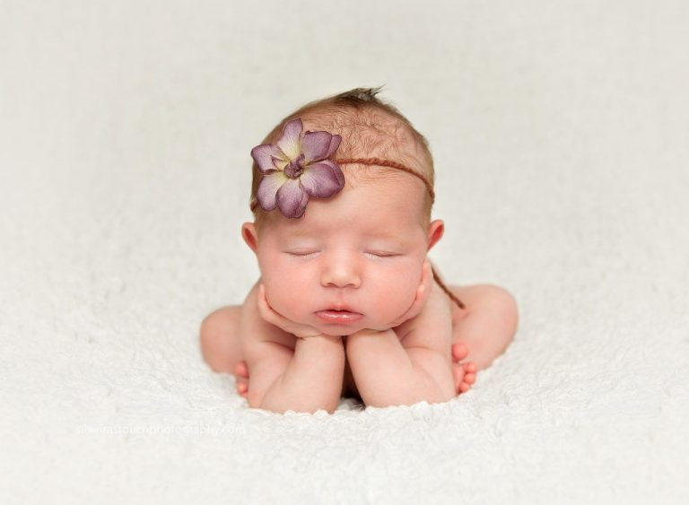 Baby wearing lilac headband sleeping with hands on chin