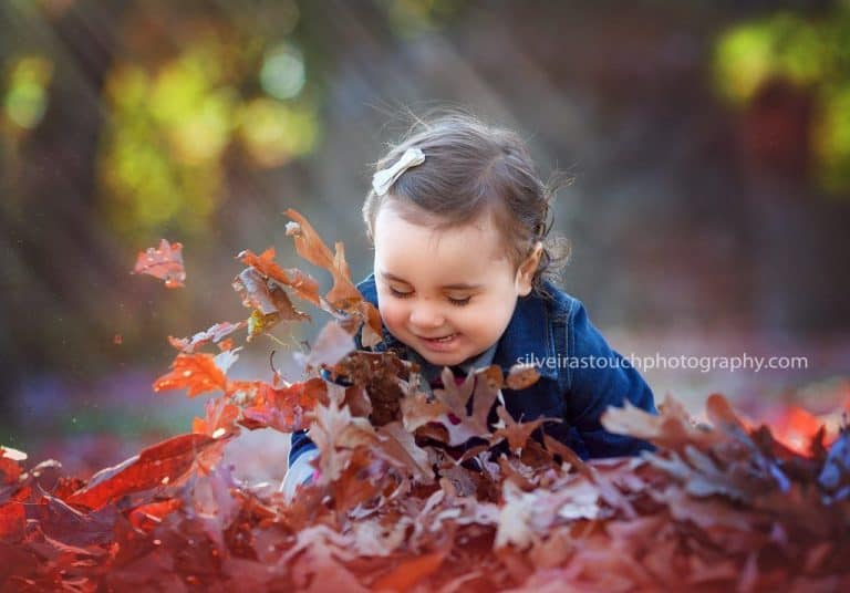 baby photo of girl jumping in leaves