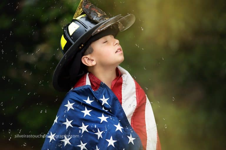 photo of boy in firefighter hat holding american flag