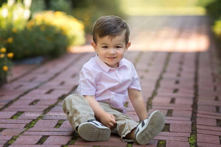 photo of toddler boy sitting and similing at arboretum