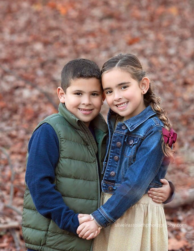 Photo of twins hugging at outdoor fall setting