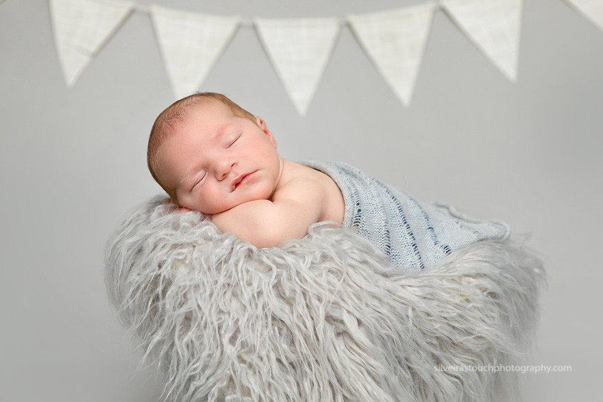 Budd Lake NJ Newborn photography of sleepy baby boy on fur in rustic bucket
