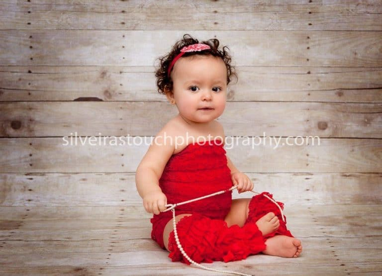 Photo of baby sistting wearing red romper