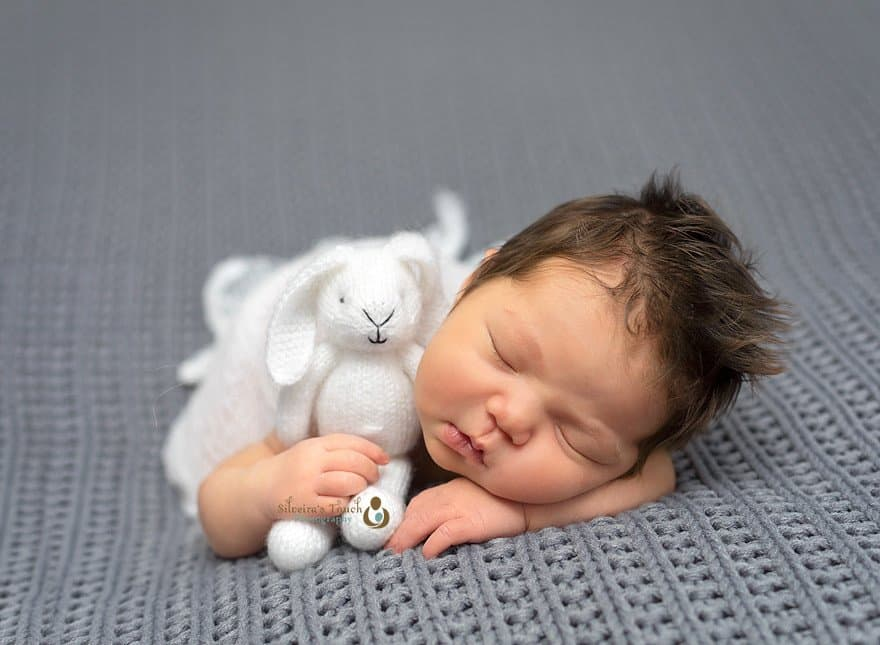 Newborn baby girlsleeping holding bunny photo