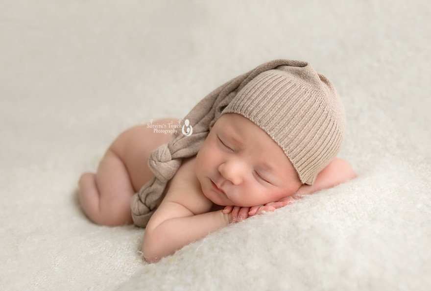 newborn photography Randolph NJ of sleepy boy in cream cap on blanket
