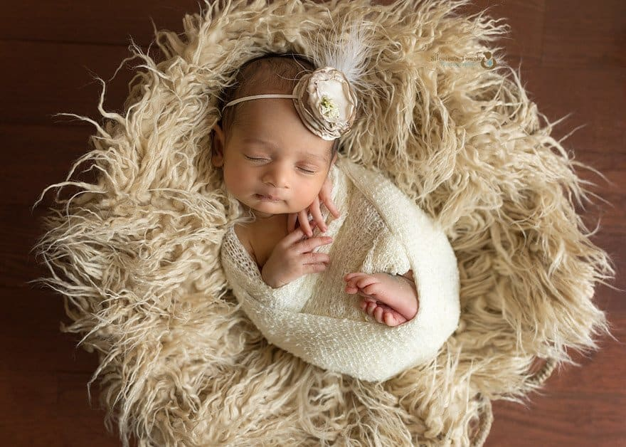 Newborn photography NJ of sleeping wrapped baby with flower headband