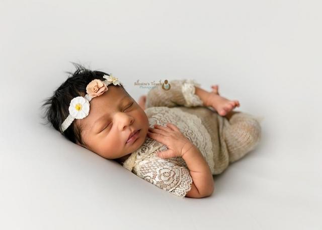Morris county NJ newborn photographer of pretty baby wearing flower headband