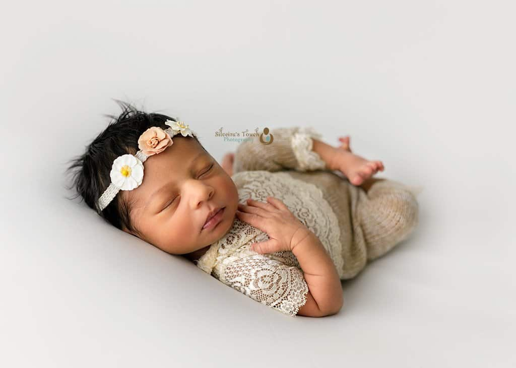 Morris county NJ newborn photographer of pretty baby wearing flower headband