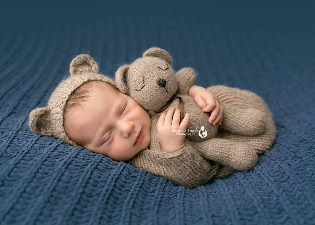 Sleepy smiling newborn baby photo holding teddy bear prop