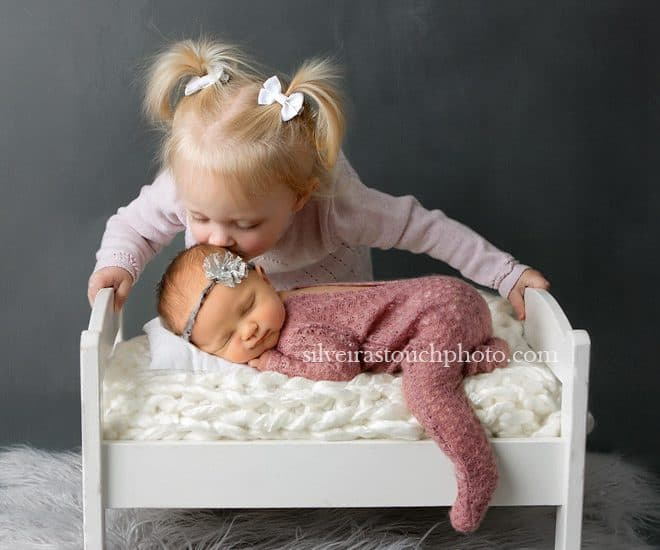 NJ newborn photography baby girl laying on tiny bed smiling with big sister kissing her head gently