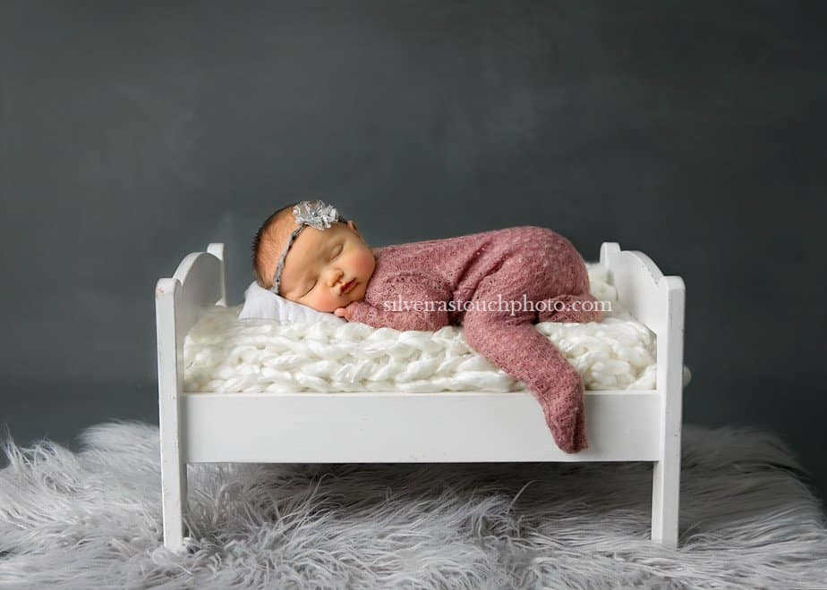 Professional newborn photographer photographing a baby girl on a baby bed posed with Soft mass on head safely