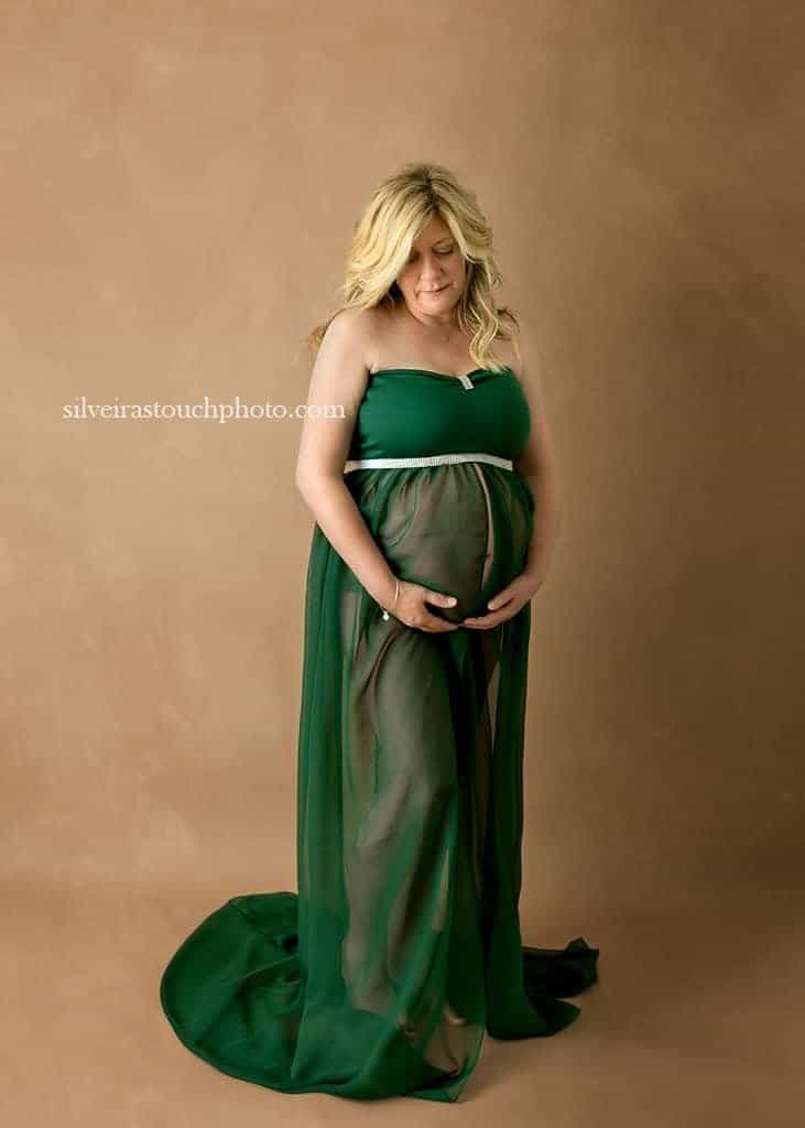maternity photography Morris County in studio session of pregnant mom to be wearing a green maternity gown