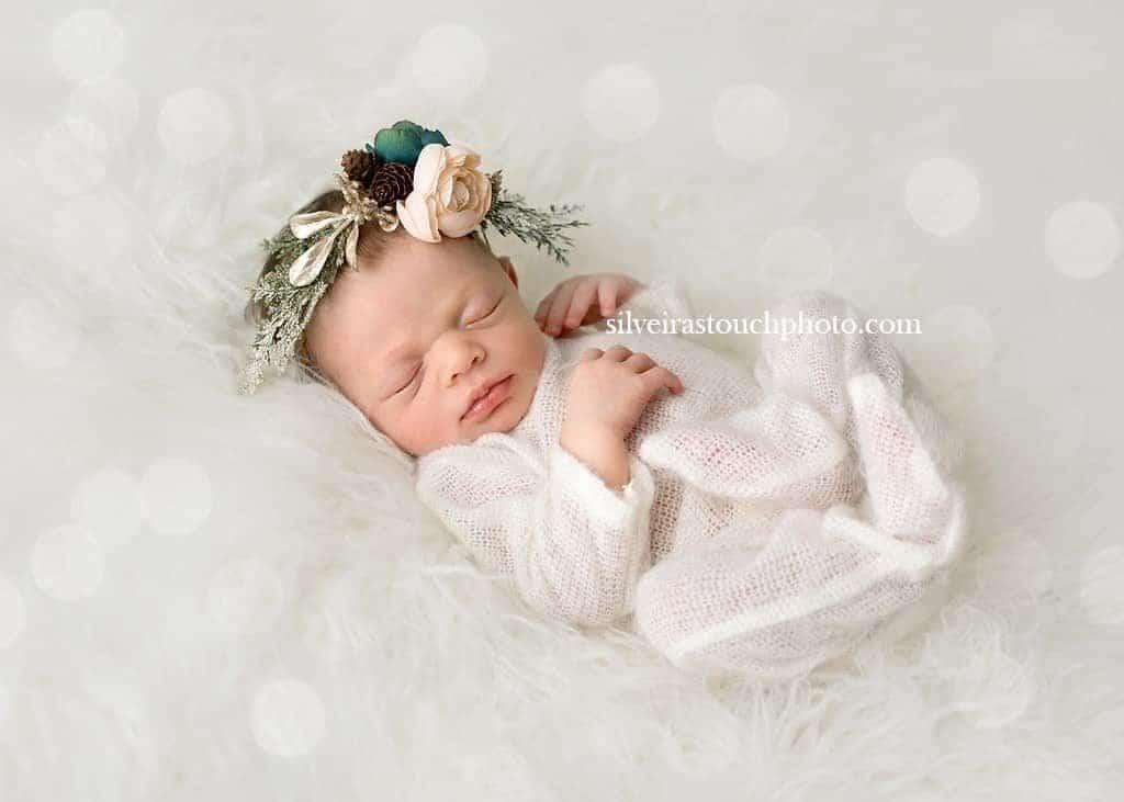 Photographing newborn baby girl on white fur