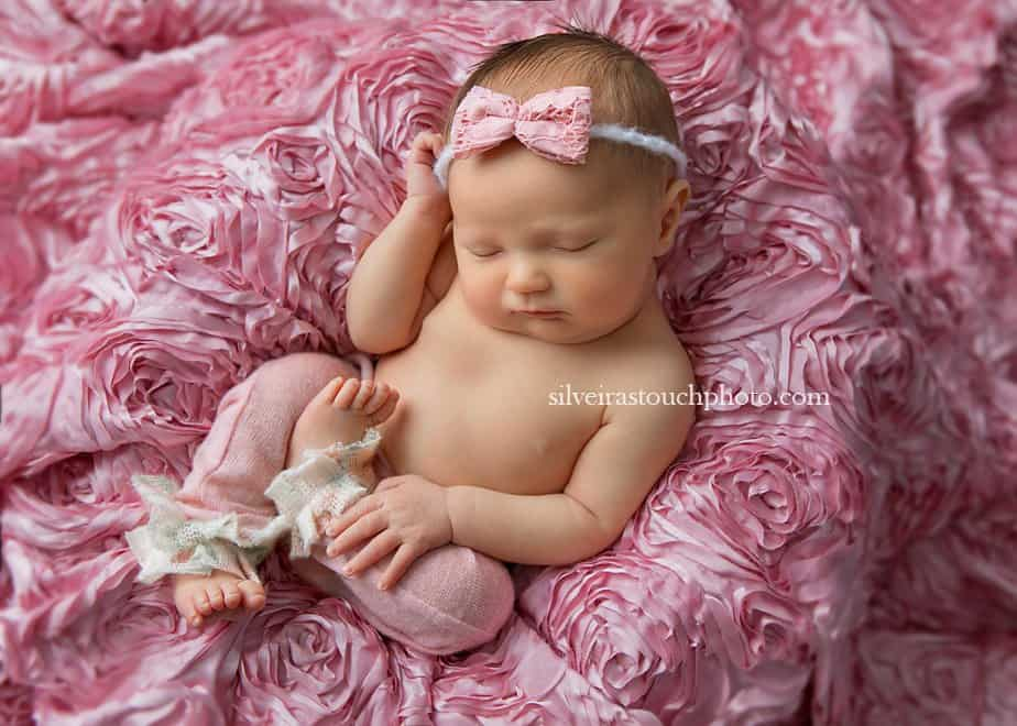 newborn baby girl laying on soft floral fabric sleeping