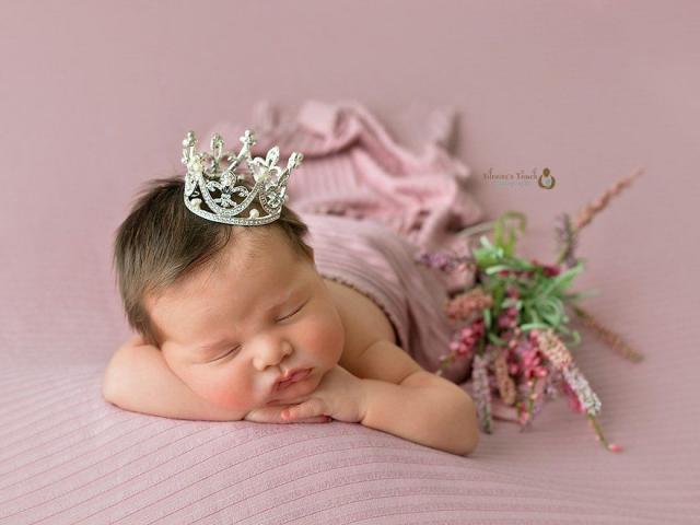 baby girl in pink wearing crown