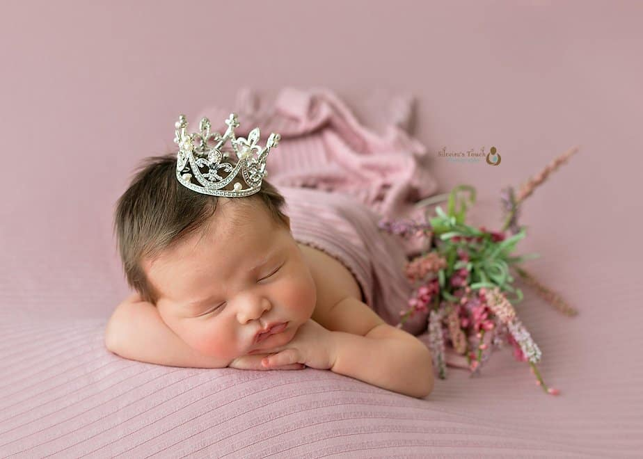 baby girl in pink wearing crown