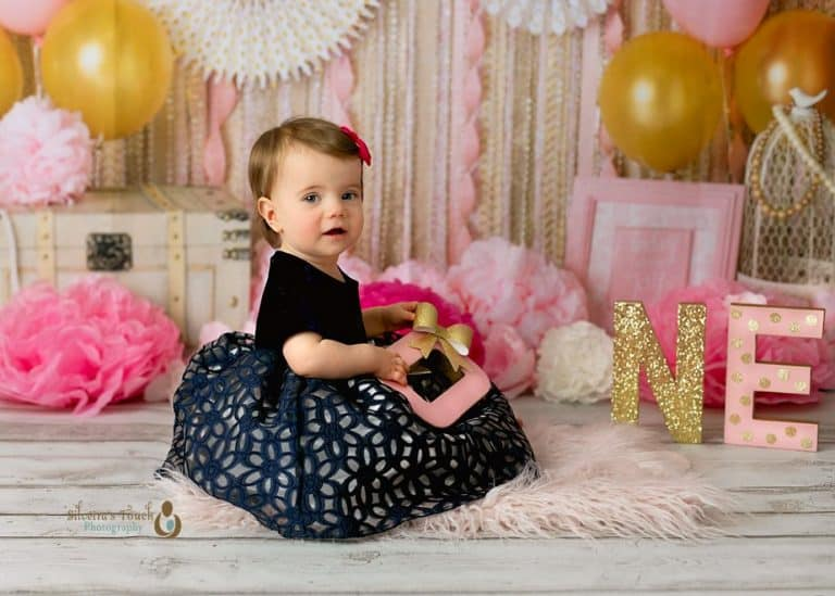 Succasunna NJ Cake smash photography of baby girl in blue dress smiling with Babydream backdrop decoration