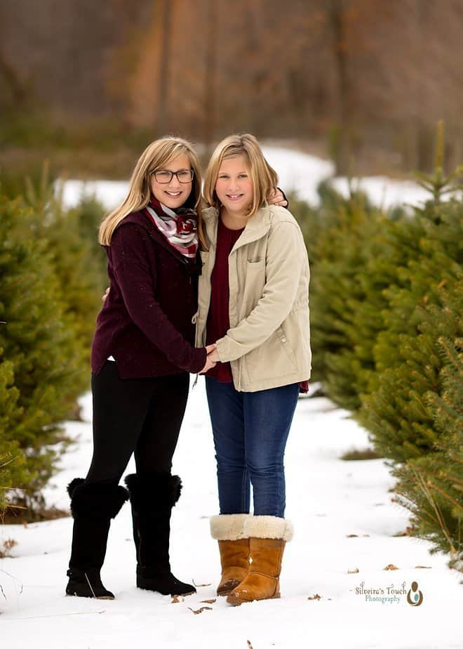 twin sister photo at tree farm smiling