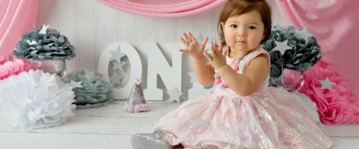 first birthday baby girl photographed with pink dress and party decorations