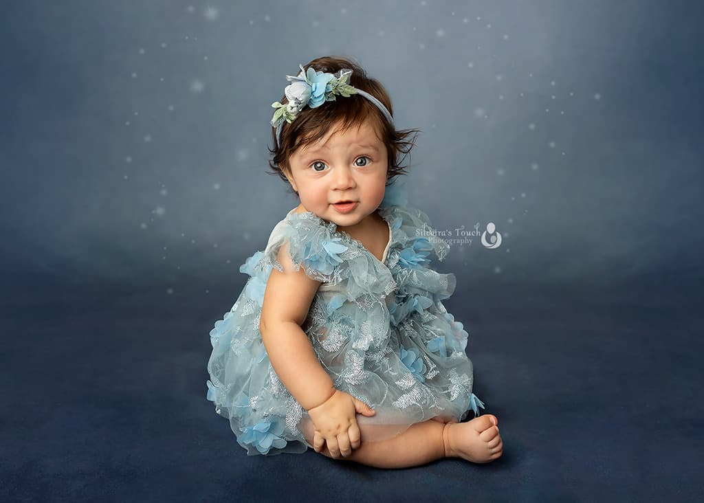 Pphoto of baby in blue couture dress smiling in studio session