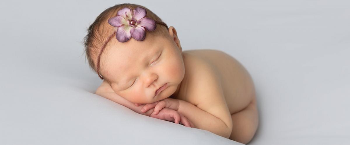 newborn-baby girl with lilac flower headband sleeping