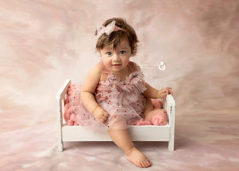 Photo of baby smiling at sitter session on baby bed