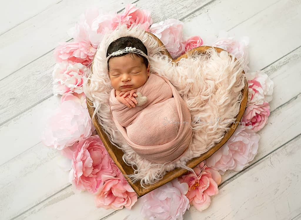 newborn baby girl in heart bowl