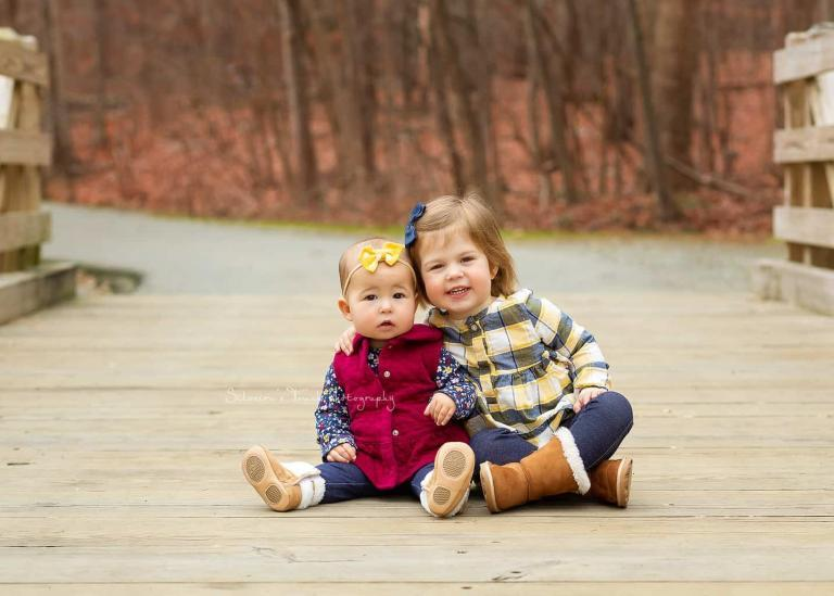 photo of big sister holding little sister smiling