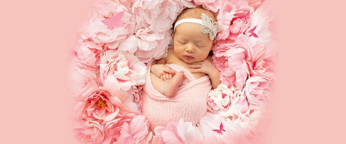 baby girl sleeping on a wreath of pink flowers