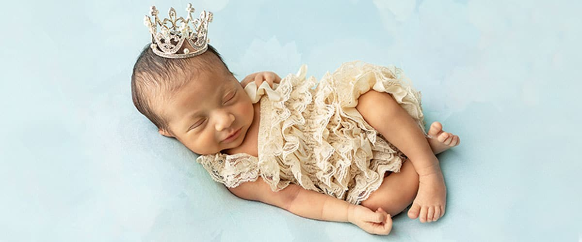 newborn girl in ruffle romper and princess crown on blue backdrop