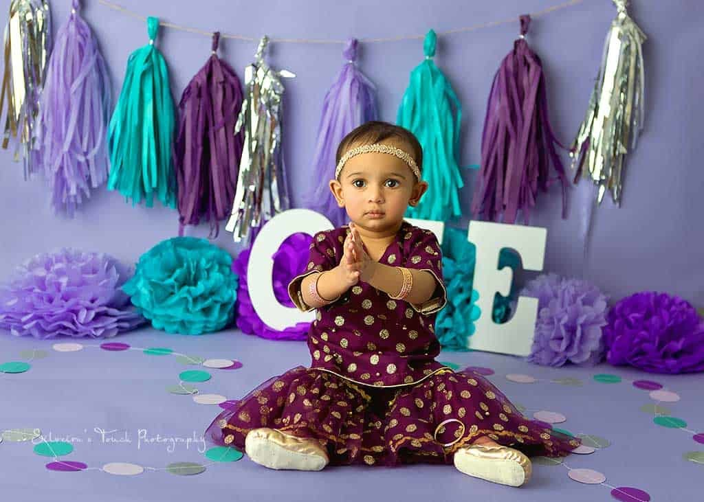 first birthday photo of baby wearing indian ethnic outfit