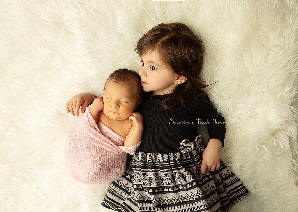newborn sibling portrait kissing