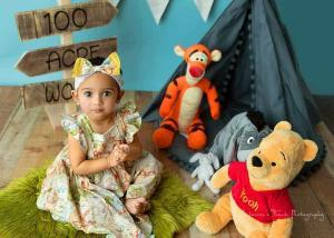 birthday photo session of girl wearing Pooh theme dress clapping
