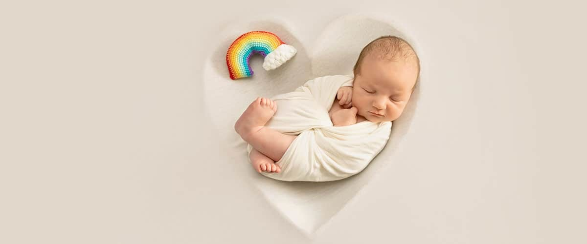 newborn boy sleeping in heart shape bowl with rainbow plush