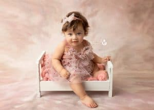 Photo of baby girl sitting on doll bed